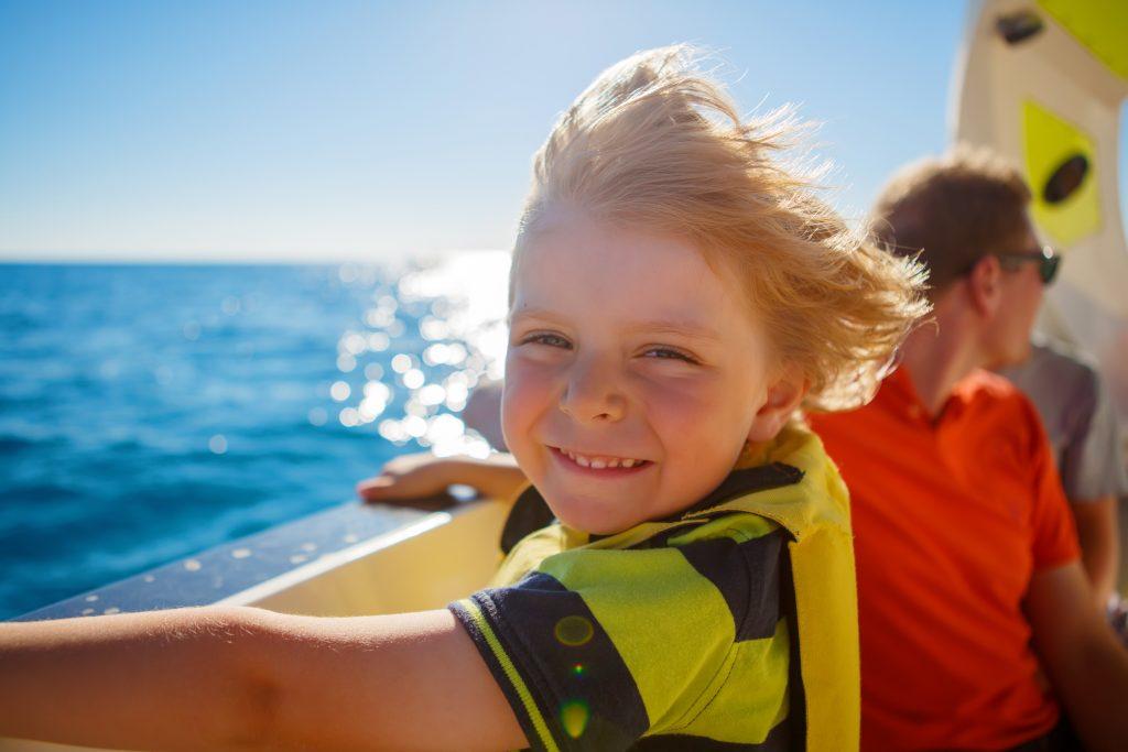 little kid boy enjoying sailing boat trip